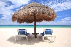 Ligstoelen onder palapa met stro bedekt zonnescherm Stock Afbeeldingen