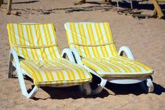 Ligstoelen op het strand stock afbeelding