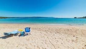 Ligstoelen op het zand in Lazzaretto-strand in Alghero royalty-vrije stock afbeeldingen