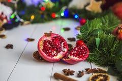 Ligt de besnoeiings rode granaatappel, kaneel, droge citroenen op witte houten lijst aangaande een achtergrond van groene Kerstmi Stock Afbeeldingen