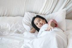 Ligt de close-up Aziatische vrouw op bed met uitnodigt iemand motie in de ochtend stock foto's