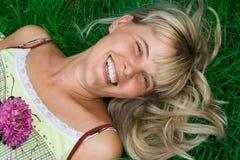 Ligt de gelukkige vrouw van de schoonheid gras Stock Foto