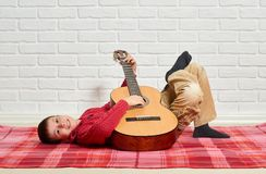 Ligt de jongens speelmuziek op gitaar, gekleed in een rode wollen sweater, op een rode geruite algemene, witte bakstenen muur op  Stock Afbeeldingen