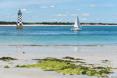 Ligthouse and boat near the Île-Tudy, bright summer day Stock Images