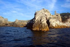Liguria: the church of Portovenere on the cliff rockview from the boat in the afternoon Stock Photography