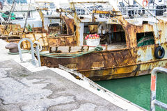 Liguria Italy - Old trawler fishing boats with fishing equipment docked in port Stock Image