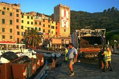 Men working to collect garbage at dawn on the pier of the port overlooking the colored buildings of Portovenere Stock Photo