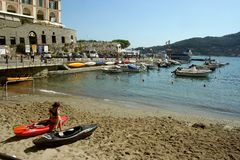Portovenere beach with woman sitting on canoes Royalty Free Stock Images