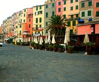 View of the colorful buildings with closed windows of Portovenere, a palm tree and cobbled umbrellas closed in front of the enclos Stock Images