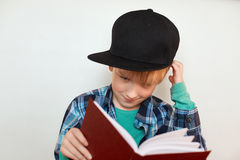 liitle好奇孩子画象有金发的在时髦的盖帽在他的手上的拿着大红色书抓他的尝试的头 免版税图库摄影