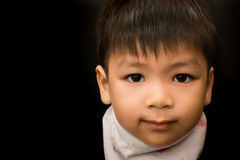 Liitle asian boy is smiling. In low key tone Royalty Free Stock Photo