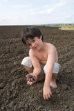 The liitle boy with  black earth Stock Photography