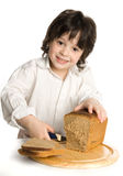 The liitle boy wich slicing a bread on desk Stock Photos