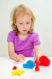 Liitle girl with plasticine Stock Images