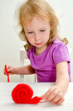 Liitle girl with plasticine Stock Photography