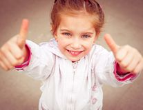 Liitle girl shows thumb Royalty Free Stock Image
