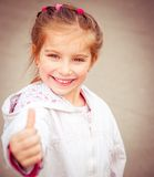 Liitle girl shows thumb Royalty Free Stock Images