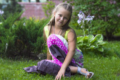 Liitle girl sitting on the grass Royalty Free Stock Photos