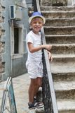 Liitle kid in a blue hat, standing on the stairs of the ancient. City Stock Image