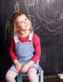 Liittle cute girl in classroom near blackboard, lifestyle people concept Royalty Free Stock Photos