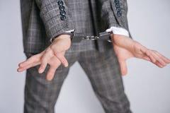 Lijdt Expensively geklede dief aan kleptomanie en voor een misdaad gearresteerd een mens in een bedrijfs modieuze kostuumtribunes royalty-vrije stock afbeelding