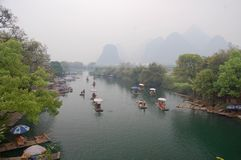 Lijiang River between Guilin and Yangshuo, China with boats cruising down the river with the misty karst mountains royalty free stock images