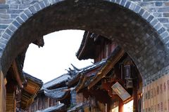 Stone arch and Chinese style roofs in the ancient city of Lijiang, Yunnan, China royalty free stock photography