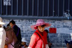 Woman in traditional costume at a village market near the ancient city of Lijiang, Yunnan, China. Lijiang, Yunnan, China - November, 2018. Woman in traditional royalty free stock images