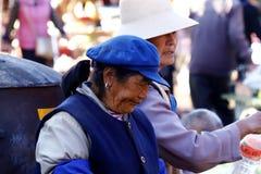 Woman in traditional costume at a village market near the ancient city of Lijiang, Yunnan, China. Lijiang, Yunnan, China - November, 2018. Woman in traditional royalty free stock photo