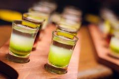 Lijn van alcohol groene schoten bij houten bureau bij barteller royalty-vrije stock afbeeldingen