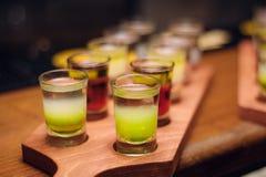 Lijn van alcohol groene schoten bij houten bureau bij barteller royalty-vrije stock foto's