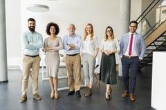 Lijn van gelukkige en positieve bedrijfsmensen die zich in het bureau bevinden stock afbeelding