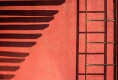 Lijn van schaduw op een rode muur Stock Fotografie
