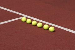 Lijn van zes gele tennisballen op hof Stock Fotografie
