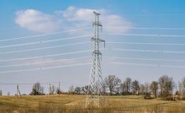 Lijnen de met hoog voltage van de steunenmacht tegen de blauwe hemel met wolken royalty-vrije stock foto's