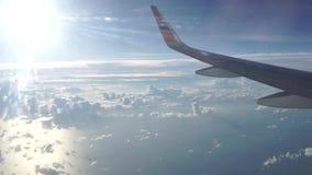 Lijnvliegtuig boven schaarse wolken vliegen en het overzees die op een zonnige dag stock videobeelden