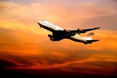 Lijnvliegtuig dat bij zonsondergang opstijgt stock afbeeldingen