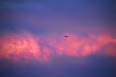 Lijnvliegtuig die in de hemel met rode wolken vliegen Stock Foto's
