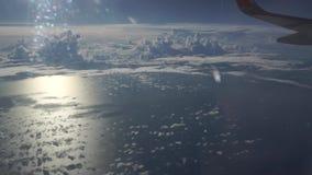 Lijnvliegtuig die hoog boven schaarse wolken en het overzees vliegen stock videobeelden