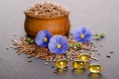 Lijnzaad in de houten kom, de schoonheidsbloemen en de olie in kappen op een grijze achtergrond royalty-vrije stock foto's