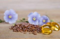 Lijnzaad, schoonheidsbloemen en olie in kappen op houten achtergrond stock afbeeldingen