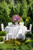 Lijst die bij een ontvangst van het luxehuwelijk in de tuin plaatsen Royalty-vrije Stock Afbeelding