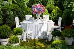Lijst die bij een ontvangst van het luxehuwelijk in de tuin plaatsen Stock Fotografie