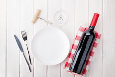 Lijst die met lege plaat, wijnglas en rode wijnfles plaatsen Royalty-vrije Stock Afbeeldingen