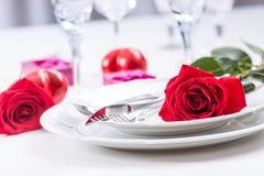 Lijst die voor valentijnskaarten of huwelijksdag plaatsen met rode rozen Romantische lijst die voor twee met de koppen en het bes stock foto's