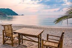 Lijst en stoelen in de zonsopgang bij een tanquilstrand in Thailand Stock Foto's