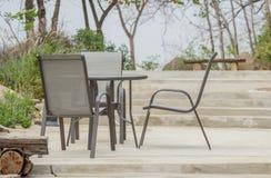 Lijst en stoelen die zich op cementvloer bevinden in de tuin Stock Afbeelding