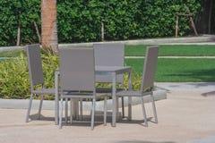 Lijst en stoelen die zich op een gazon bij de tuin in de toevlucht bevinden Stock Foto