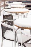 Lijst en stoelen met sneeuw in openluchtkoffie in de winter Stock Foto's
