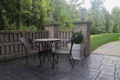 Lijst en stoelen op terras in ochtendlicht stock afbeelding